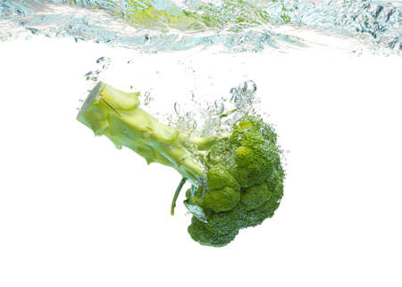 Green broccoli falling in water with splash on white with air bubbles.
