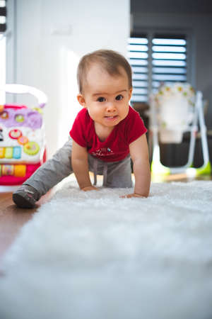 Baby on all fours in bright room. Baby development concept. Reklamní fotografie