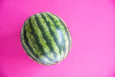 Green watermelon on pink background top view Stock Photo