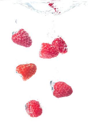 Raspberries splashing in water on white