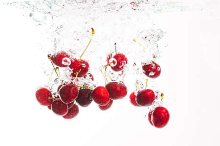 Red cherries splashing into crystal clear water with air bubbles. Isolated on a white background.
