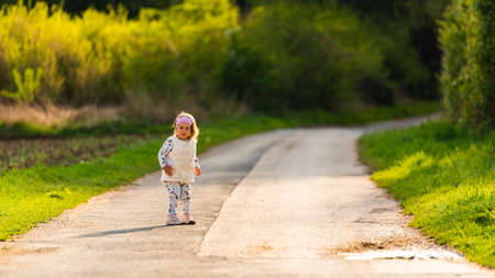 Child on walk outdoors on a rural road leading to forest. Stock Photo