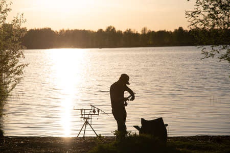 A fisherman silhouette fishing at sunset. Stock Photo