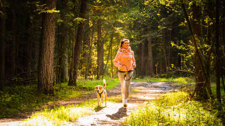 Young woman and dog running together in sunny forest. Stock Photo