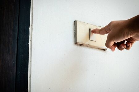 Hand switching the old lighting switch on white cement or concrete background Stock Photo