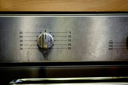 A stained oven countdown timer stainless steel adjustable knob on wooden background