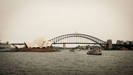 December 29, 2019 - Sydney, Australia: A perspective view of the Harbour Bridge with the Opera House looking from the cruise ship with two small tourist ships cruising in the river Фото со стока