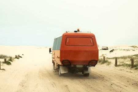 A red off-road truck driving in the desert or sand dunes near Port Stephens of New South Wales, Australia