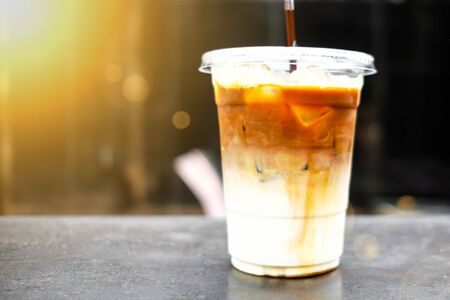 A close-up shot of iced caramel macchiato served in a plastic cup, placed on the rusty metal table, with a blurred background inside the cafe