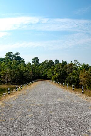 A gravel road with no people in the middle of trees and lakes at the famous national park in Thailand 版權商用圖片