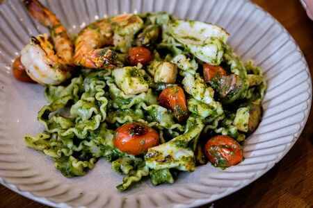 Delicious Reginette pasta with seafood and pesto sauce on a modern plate, blurred background