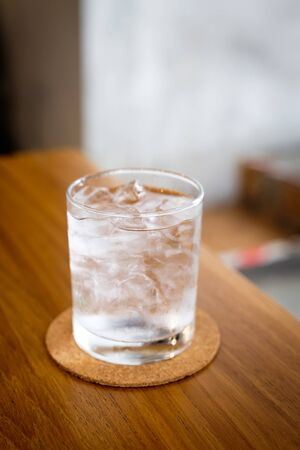 A glass of cold drinking water with ice served with a coaster on wooden table, with blurred background Stockfoto
