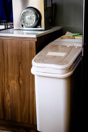 A white plastic garbage bin with clear cover standing beside wooden cabinet inside the restaurant