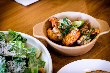 Freshly delicious grilled Gambas al Ajillo, Spanish style sizzling chilli-and-garlic Tapas shrimp pinchos, served on a wooden table