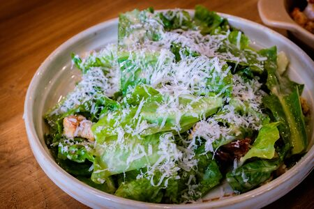 A healthy white-plated delicious fresh caesar salad on a wooden table Stockfoto