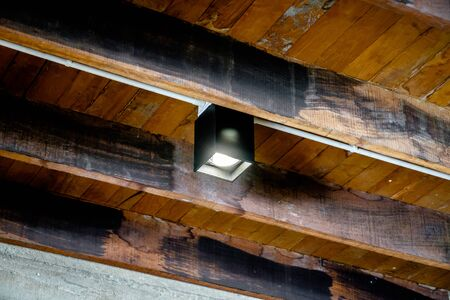 Grey modern and decorative square prism LED downlight from antique wooden ceiling environment