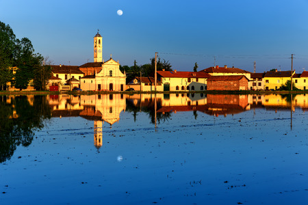 Typical Italian Lanscape of a rice field with Houses and Rice Paddy with water Blue Sky with moon and the houses, mirrored on the Rice Paddyligheted by the sunset  photo
