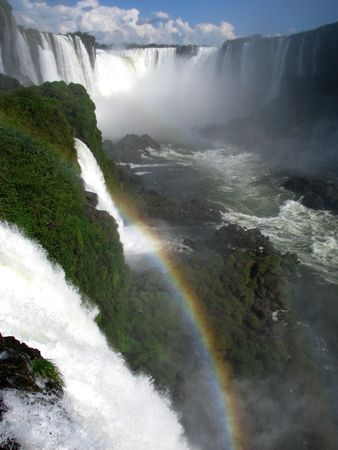IGUAZU WATER FALLS, with a rainbow following down the water. Brasil Stock Photo