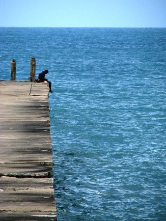 Young man on a pier staring at the Atlantic ocean in Fortaleza, north-eastern Brazil. Stock Photo