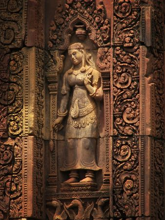 Lovely Apsara (dancing woman) red sandstone carving at the Banteay Srei temple (temple of women) near Angkor Wat (Siem Reap, Cambodia).