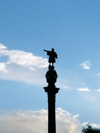 christopher columbus: Barcelona symbol  statue of Christopher Columbus pointing to America, silhouetted against blue cloudy sky, near the seaside and the port  Barcelona, Catalonia, Spain