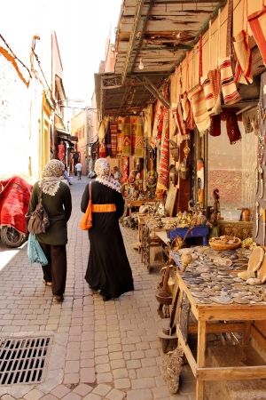 Moroccan women in the colorful streets of the main souk of Marrakesh, Morocco