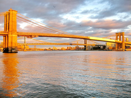 Brooklyn Bridge and East River at sunset, seen from historic Pier 17  New York City, USA
