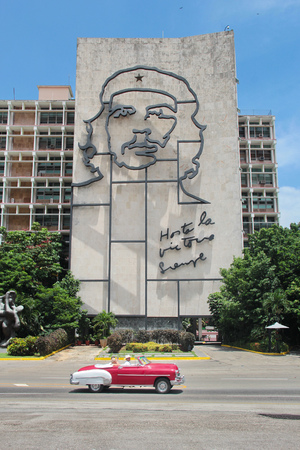 HAVANA, CUBA, AUGUST 16, 2016: Vintage car drives in front of iconic iron mural of Che Guevaras face on Ministry of Interior building, at the Revolution Square in Havana, Cuba Editorial