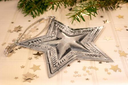 silver star on white tablecloth with stars and pine branches Stock Photo