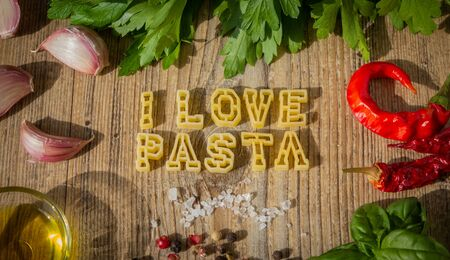 Uncooked pasta letters make up the word I love pasta. photo set.