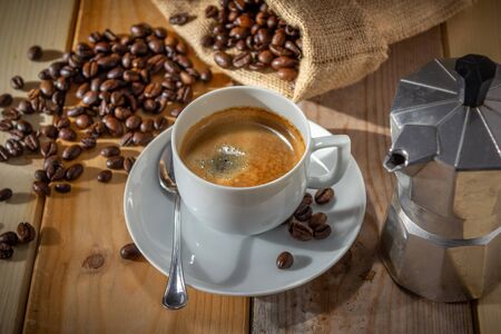 coffee in ceramic cup, moka coffee machine, coffee beans and burlap sack on wooden background
