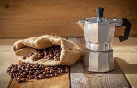 Moka coffee machine, coffee beans and burlap sack on wooden background