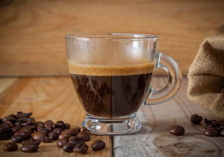 coffee in glass cup, coffee beans and burlap sack on wooden background