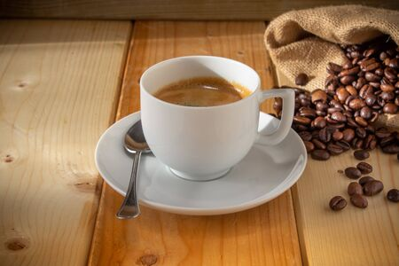 coffee in ceramic cup, coffee beans and burlap sack on wooden background Stock fotó