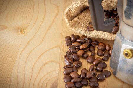 moka coffee machine, coffee beans and burlap sack on wooden background Stock fotó