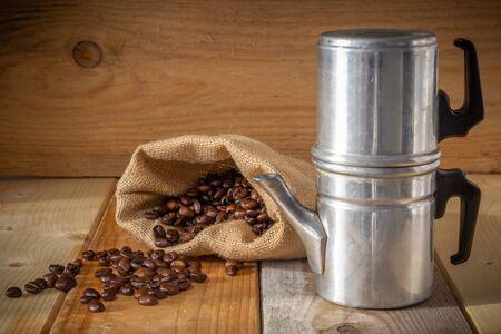 Neapolitan coffee machine, coffee beans and burlap sack on wooden background Stock fotó