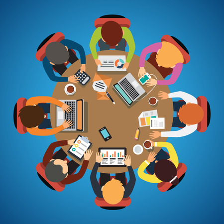Eight people team sitting and working together at the round table.