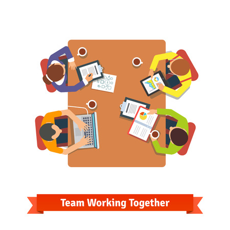 sitting at table: Top view of a team working together on a project in a conference room.