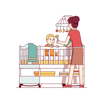 Mother playing with baby son sitting in crib bed