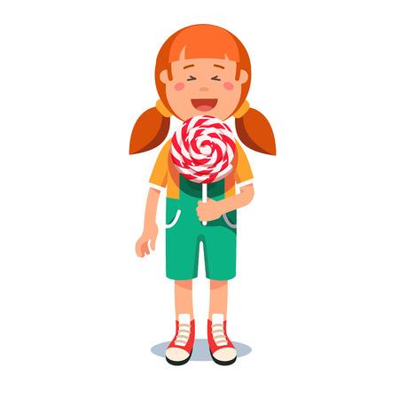 first grader: Cute little girl standing with big swirly lollipop