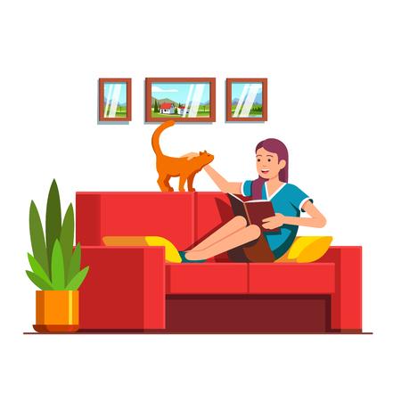 Woman sitting on sofa, reading book, petting cat.