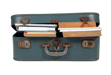 Leather suitcase filled with books on white background photo