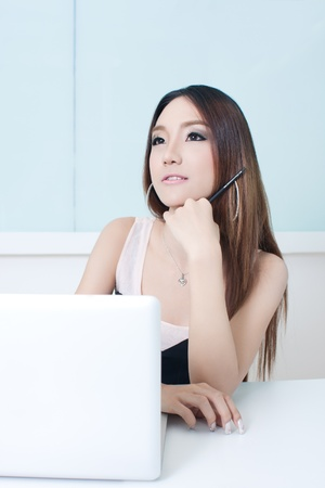 Pensive businesswoman at desk with laptop photo