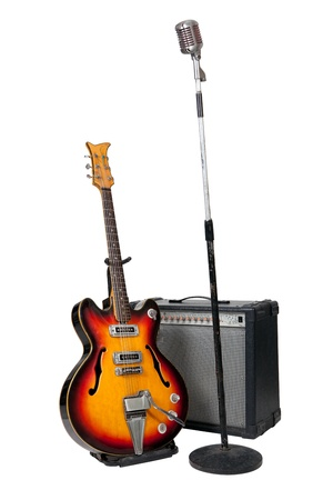 Vintage microphone on stand with guitar and amplifier on white background