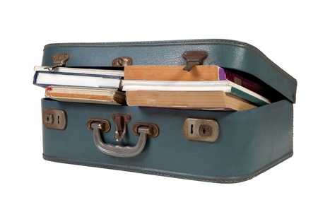 Leather suitcase filled with books on white background