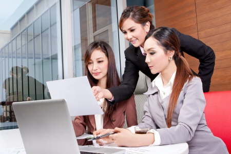 colleague: Group of business people on a laptop in an office