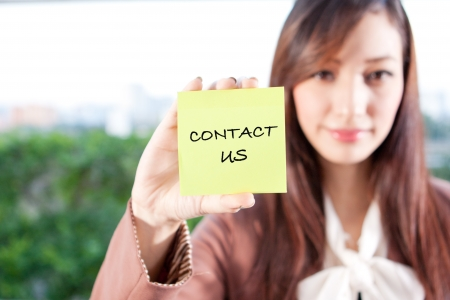 Beautiful businesswoman showing contact us text on a note photo