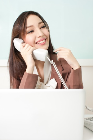 Beautiful young business woman sitting at her desk , speaking on the telephone Stock Photo