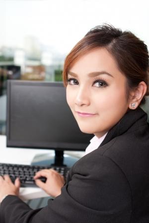 Portrait of beautiful woman sitting in front of desktop computer