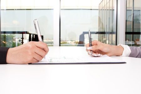 Hands of business people sitting at desk with documents sign up contract